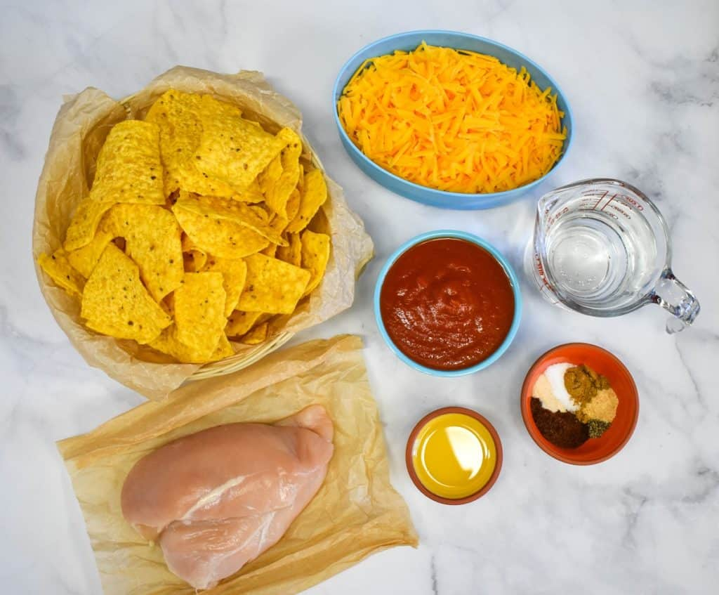 The ingredients for the shredded chicken nachos, except the topping, displayed on a white table.