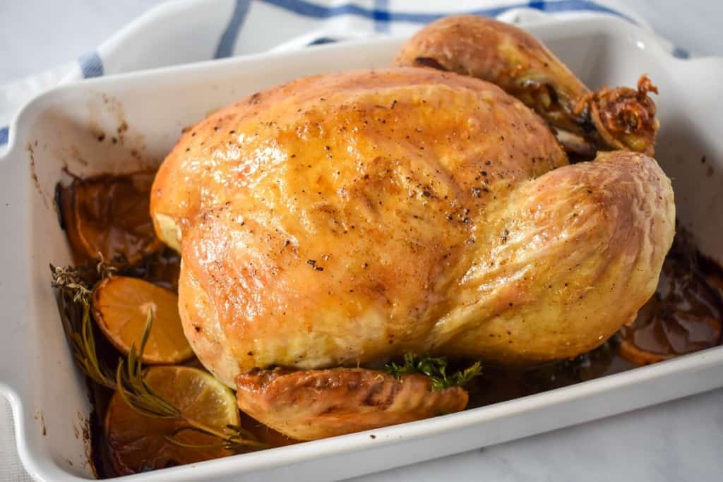 The whole roasted chicken in a white casserole dish and the pan juices and roasted lemon slices and herbs.