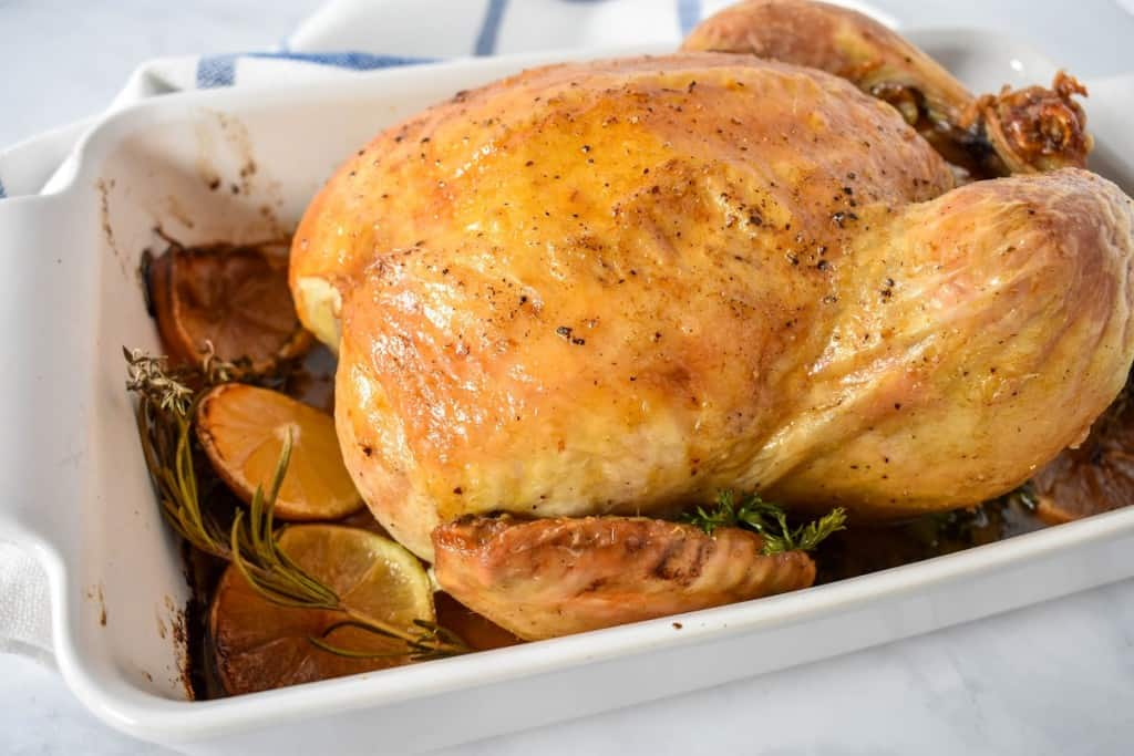 An image of the whole roasted chicken in a white casserole dish in the pan juices with the roasted lemon slices and herbs arranged around it.