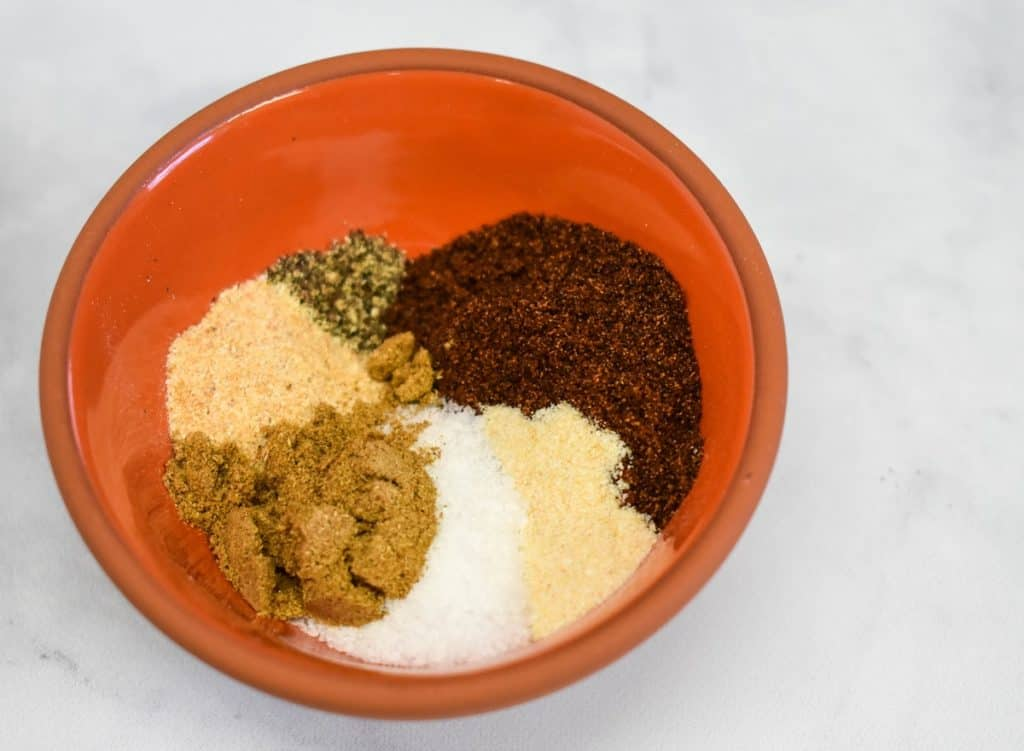 The spices in the taco seasoning in a small orange bowl before being mixed.