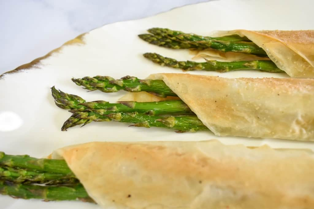 The finished asparagus rolls set on a white platters with gold trim.