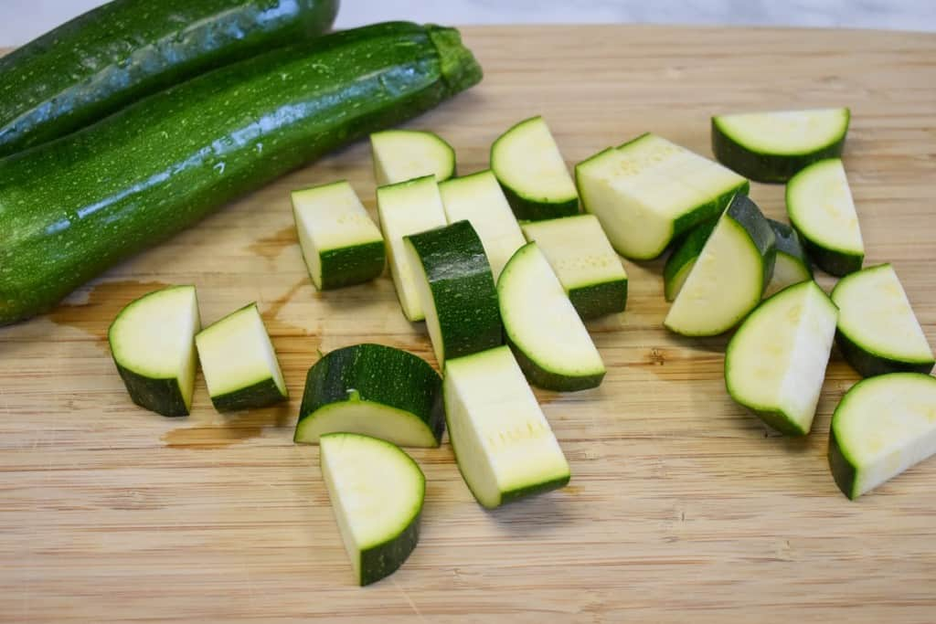 Zucchini on a cutting board with one cut into roughly one inch pieces.