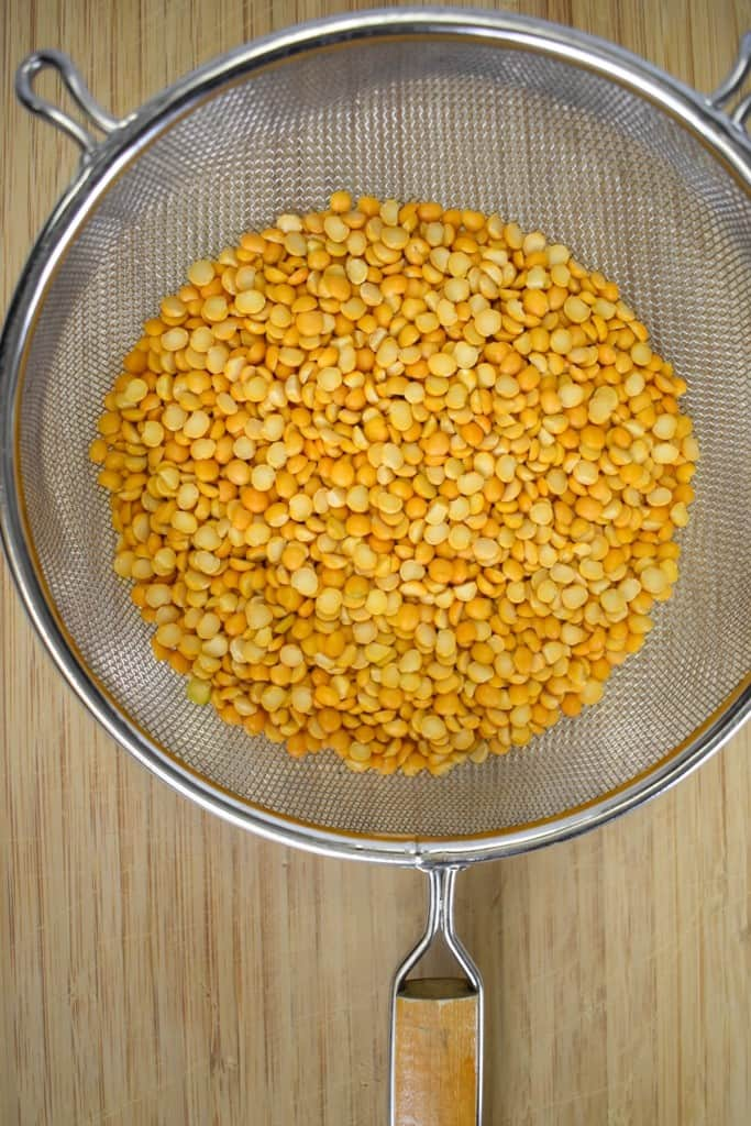 Yellow split peas in a large mesh strainer set on a wood cutting board.