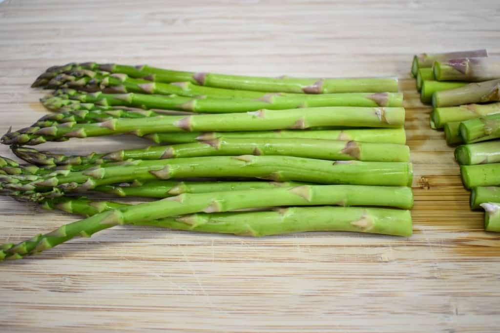 Asparagus with the ends trimmed off on a wood cutting board.