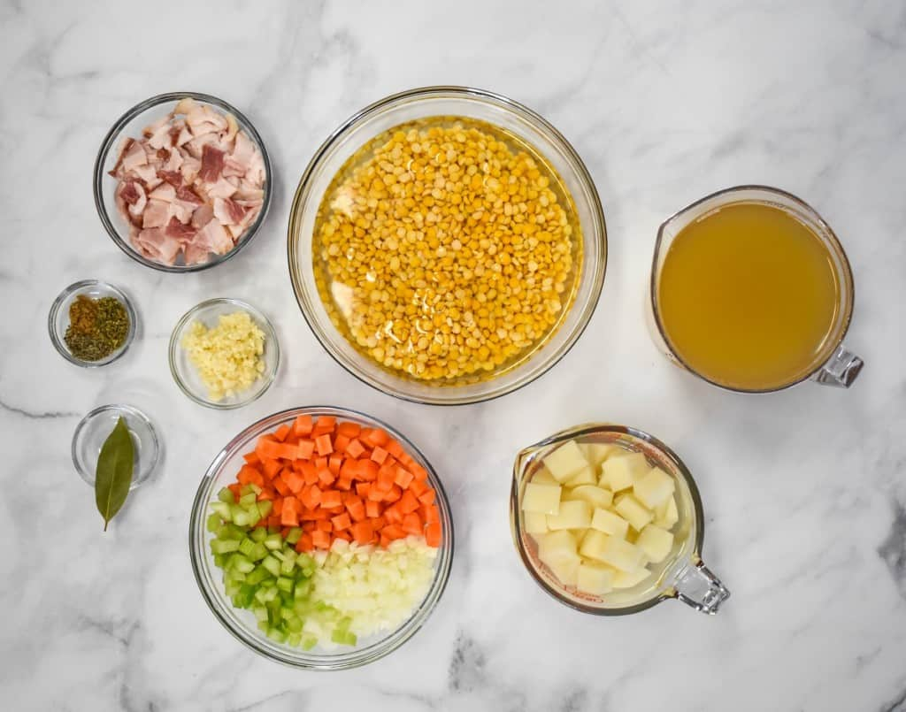 The prepped ingredients for the soup separated in clear containers and arranged on a white table.