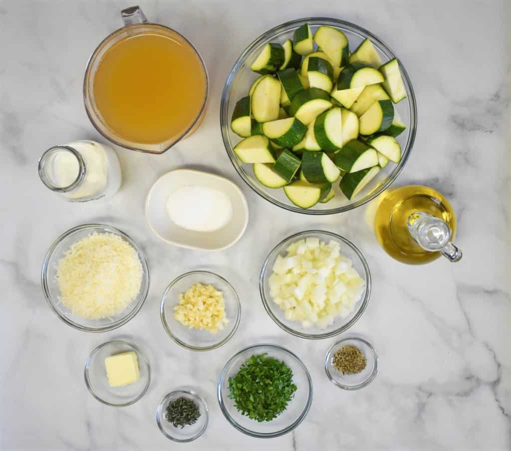 The ingredients for the soup prepped and separated into clear bowls, displayed on a white table.