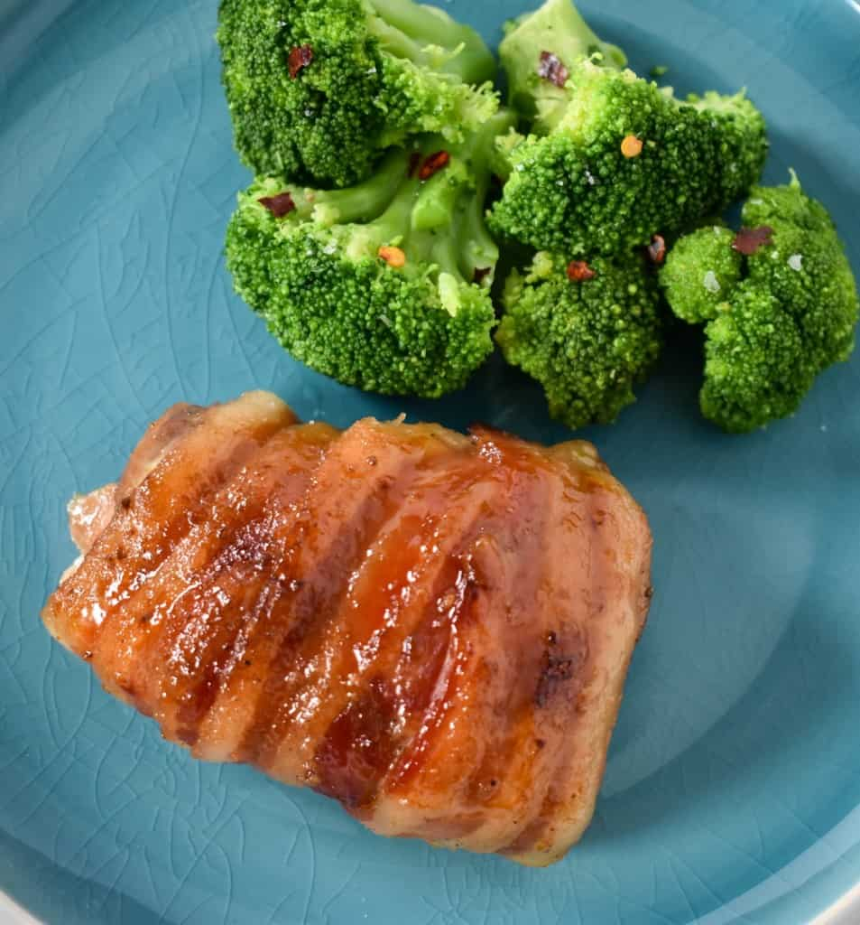 The bacon wrapped chicken thighs served on a aqua colored plate with a side of steamed broccoli garnished with a little crushed red pepper.