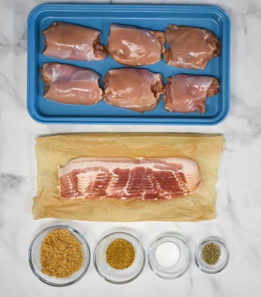 The ingredients for the dish arranged on a white table. The chicken is in a blue pan, the bacon on parchment paper and the seasoning in small glass bowls.
