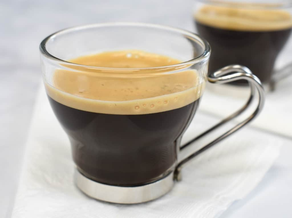 Cuban coffee served in a clear espresso cup and set on a white napkin.