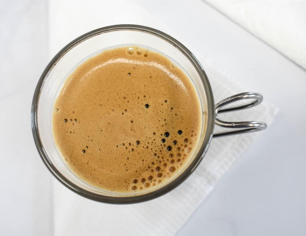 A top shot image of coffee in an espresso cup featuring the foam.