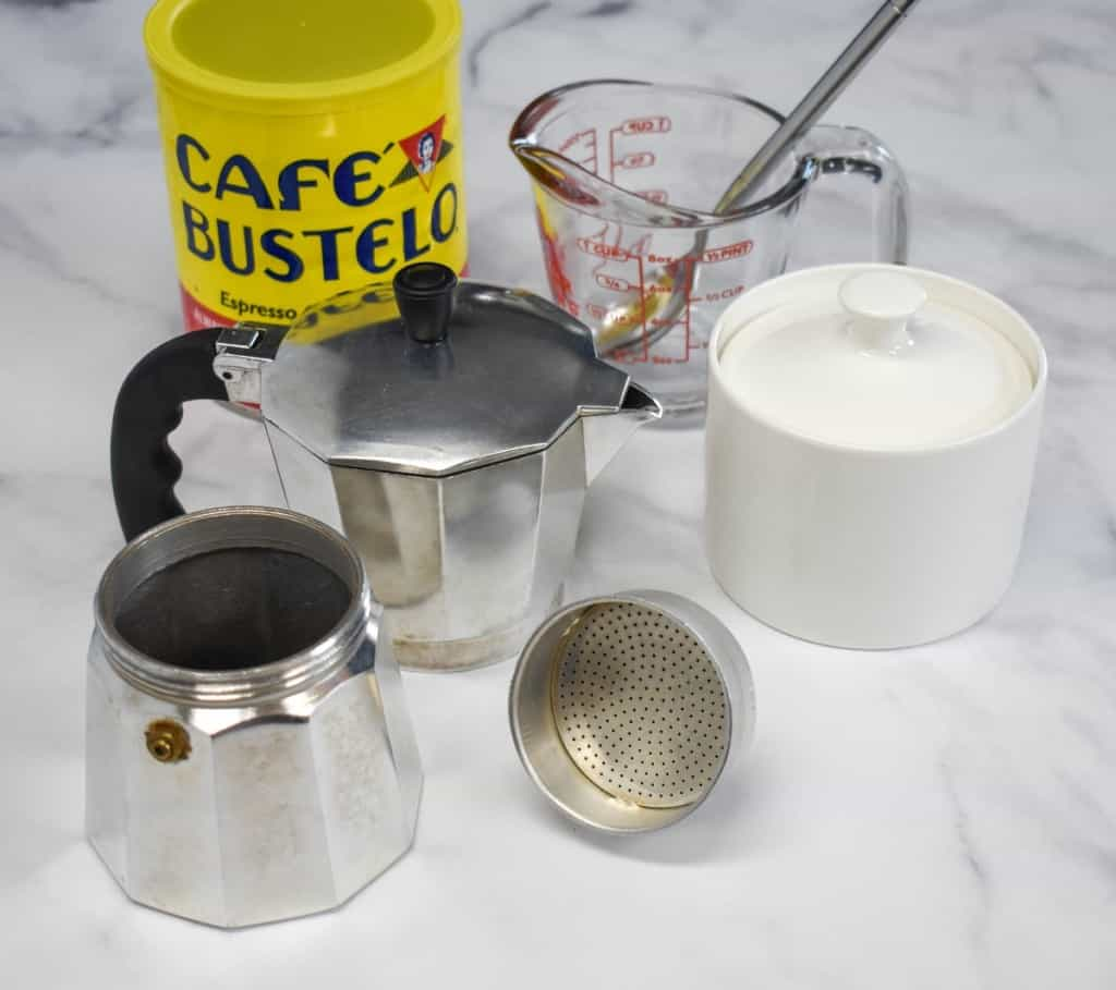 The ingredients and appliance used to make Cuban coffee arranged on a white table.