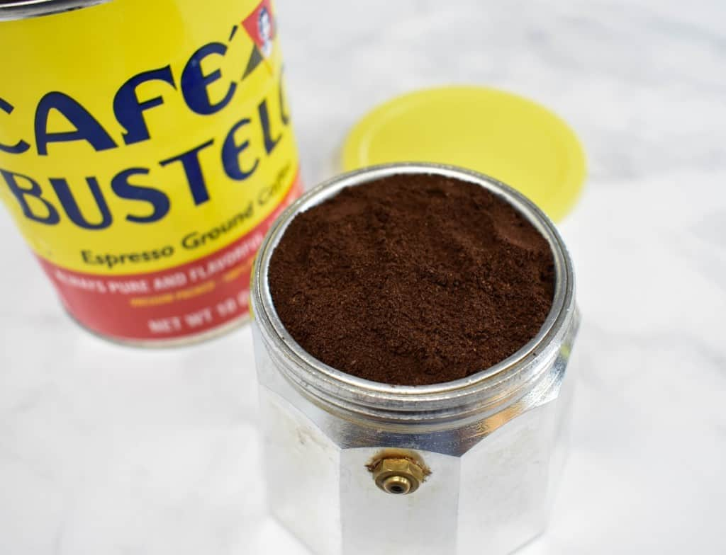 The coffee pot base with the filter inserted filled with the espresso grounds. There is a yellow tin can of coffee in the background.