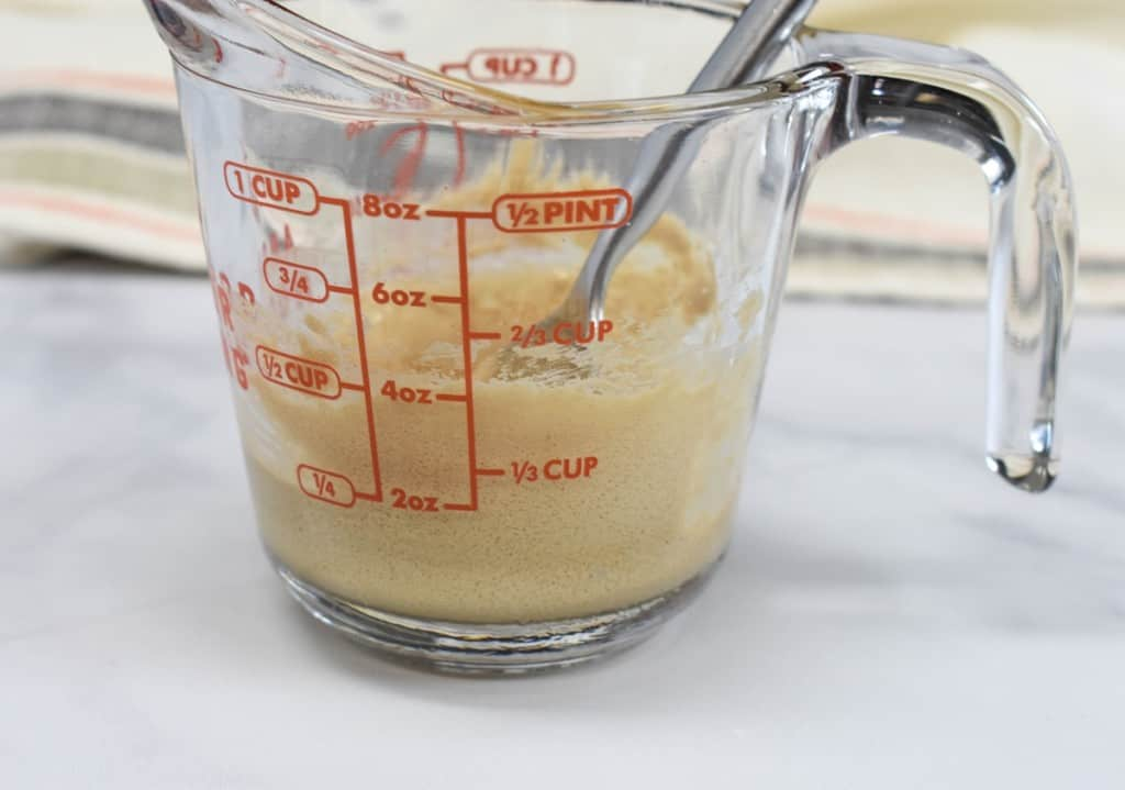 A glass measuring cup with the sugar coffee mixture beaten together to form a light beige mixture.