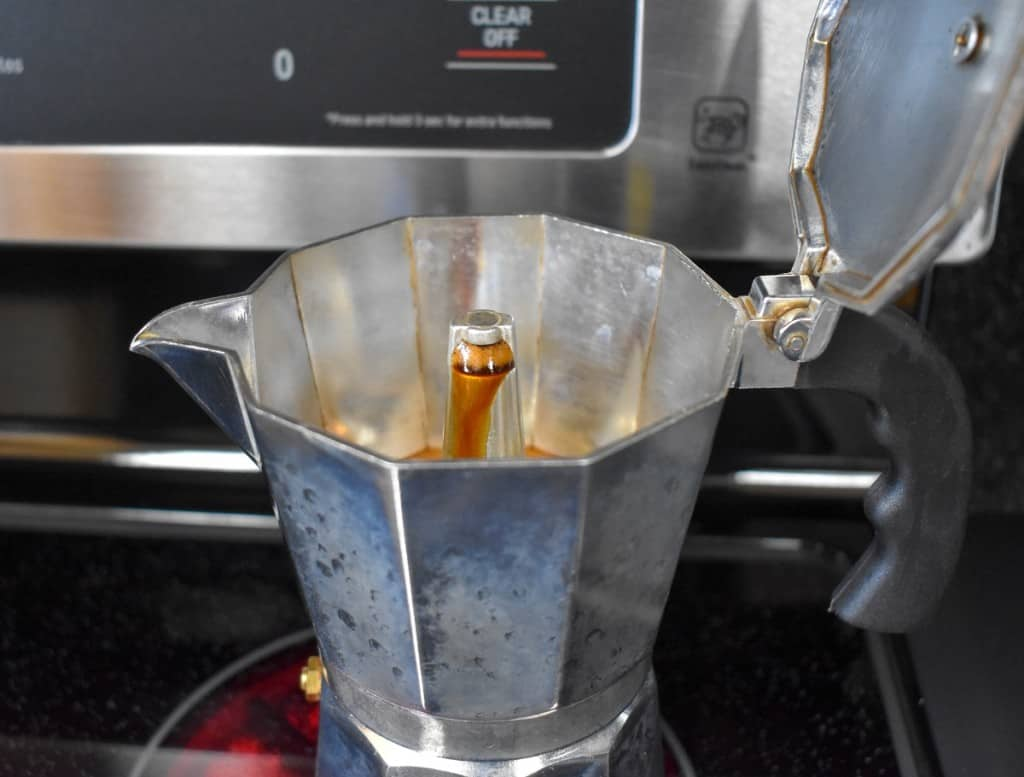 A close up of the stovetop coffee pot with coffee coming out of the brewing tip.