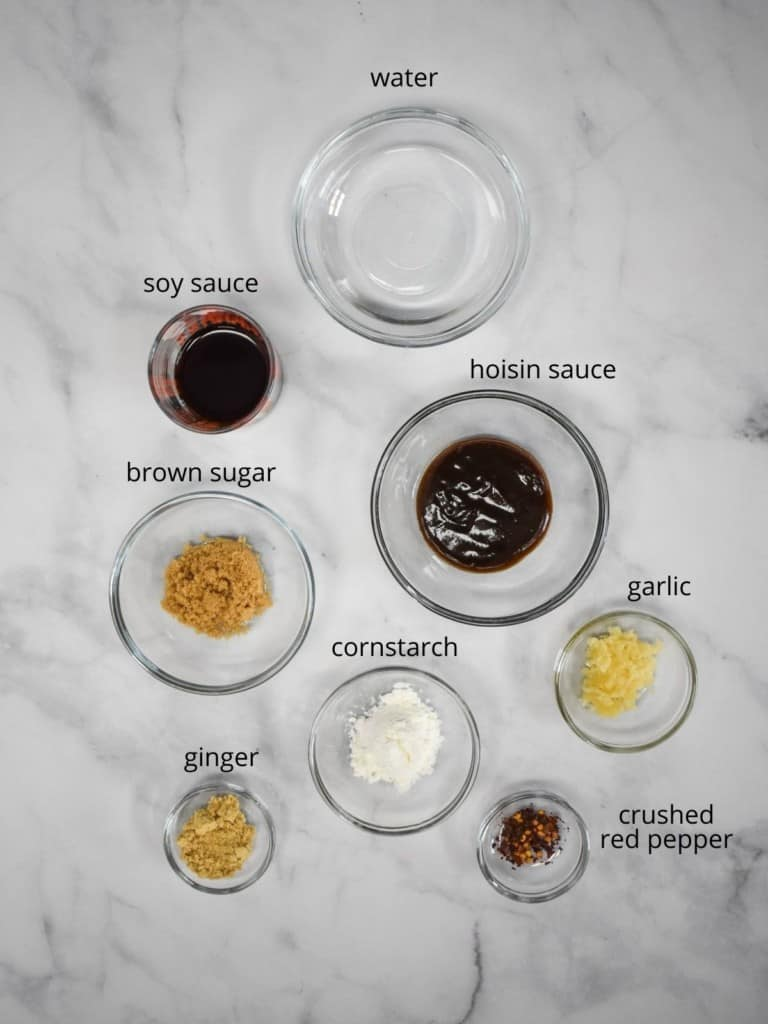 The ingredients for the stir fry sauce arranged in glass containers on a white table. Each ingredient has the name in small black letters next to it.