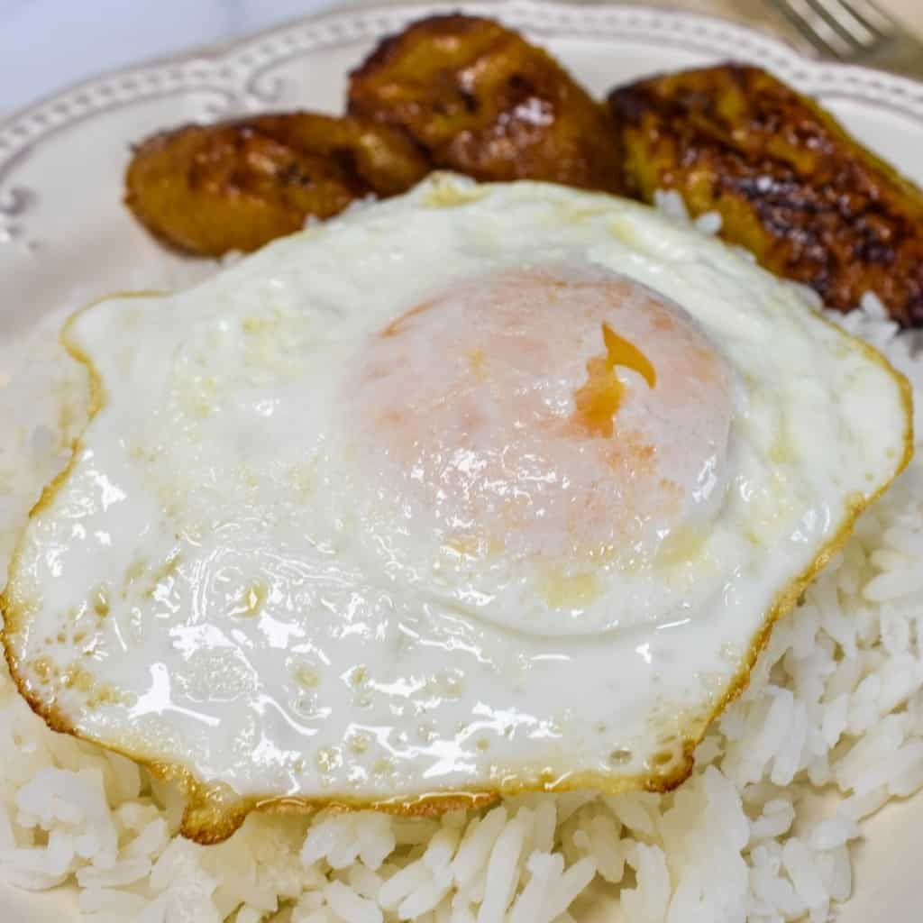 A close-up image of the arroz con huevo frito with sweet plantains served on an off-white plate.