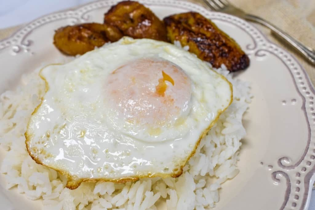 A fried egg on a bed of white rice with fried sweet plantains on the side served on an ornate off-white plate.
