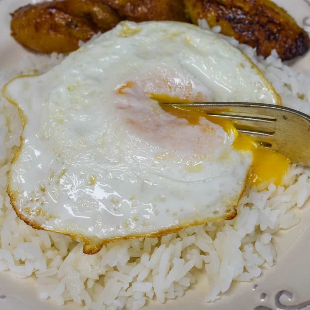 A close up of the arroz con huevo frito with a fork cutting into the yolk and served with sweet plantains.