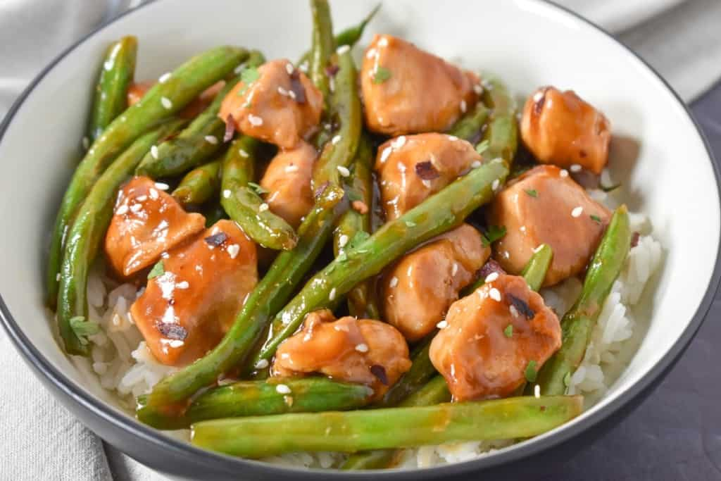 A close up image of the chicken and green beans served on a bed of white rice in a white bowl with a black rim.