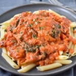 An image of the creamy tomato chicken on a bed of penne pasta served on a gray plate and garnished with chopped parsley.