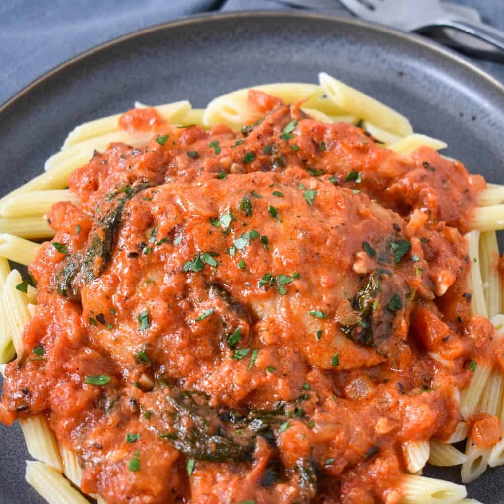 A close up of the finished dish served on a bed of penne pasta on a gray plate and garnished with chopped parsley.