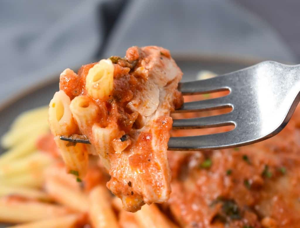 A close up of a slice of chicken and pasta covered in tomato sauce on a fork held over the finished plate.