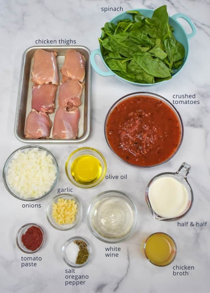 The ingredients for the dish prepped and arranged on a white table in separate bowls and containers.