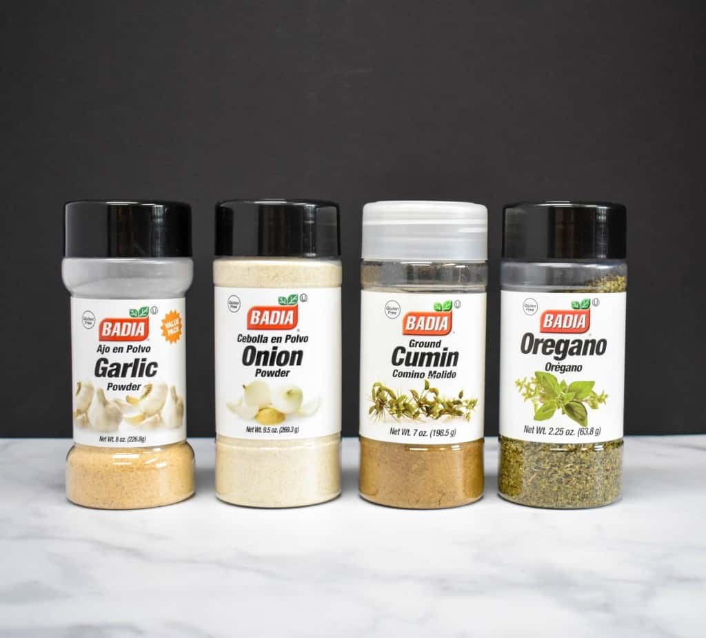 Containers of garlic powder, onion powder, cumin and dried oregano lined up on a white table with a black background.