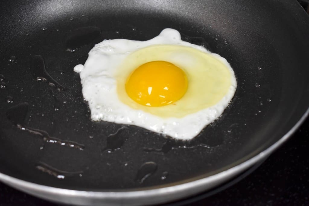 An egg cooking in a non-stick skillet, the yolk is not cooked but the egg white is almost set around it.