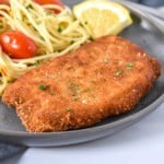 An image of a breaded fried pork chop with spaghetti and small tomatoes in the background and a lemon wedge on the side. The meal is served on a gray plate set on a white table.