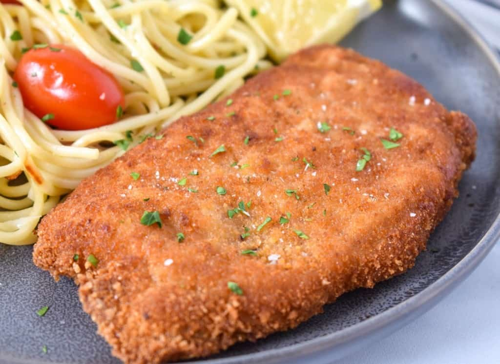 An image of a breaded fried pork chop with spaghetti and small tomatoes in the background and a lemon wedge on the side. The meal is served on a gray plate.