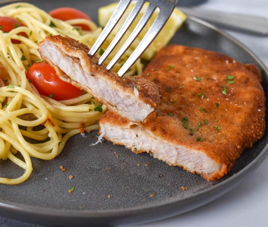 A close up image of the cut piece of fried pork chop held up by a fork. In the background is the remaining piece served with spaghetti with tomatoes. The meal is served on a gray plate.
