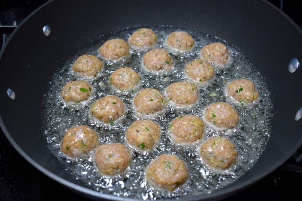 The meatballs in a large, black skillet frying in oil.