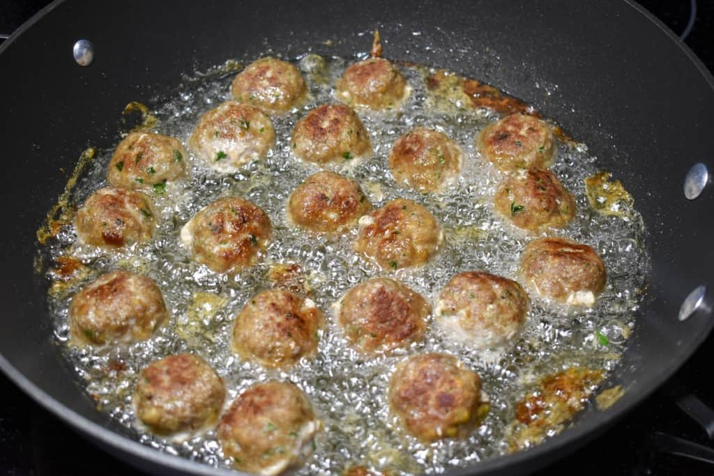 Frying meatballs in a large, black skillet with the browned side up.