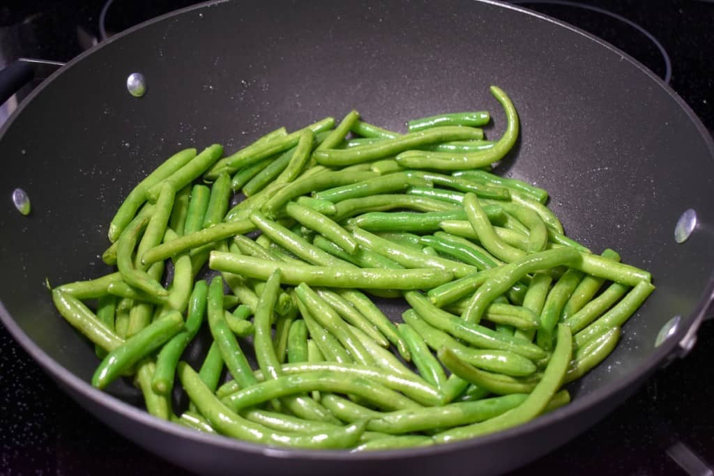 Green beans in a large, black skillet.