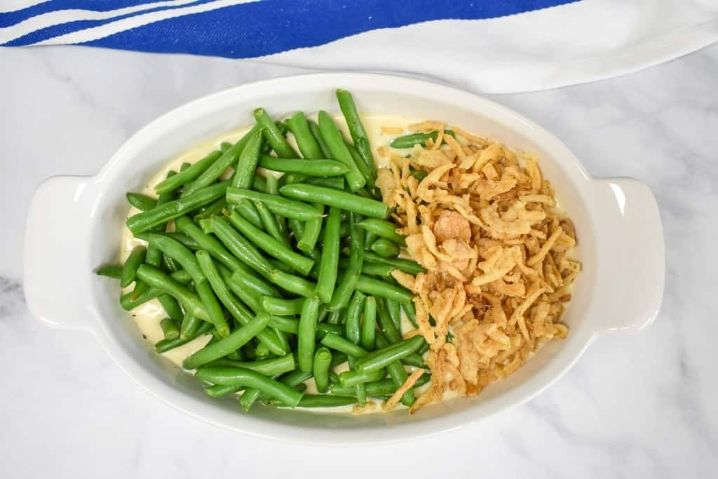 Green beans to the left and crispy fried onions to the right in a casserole dish before being stirred.