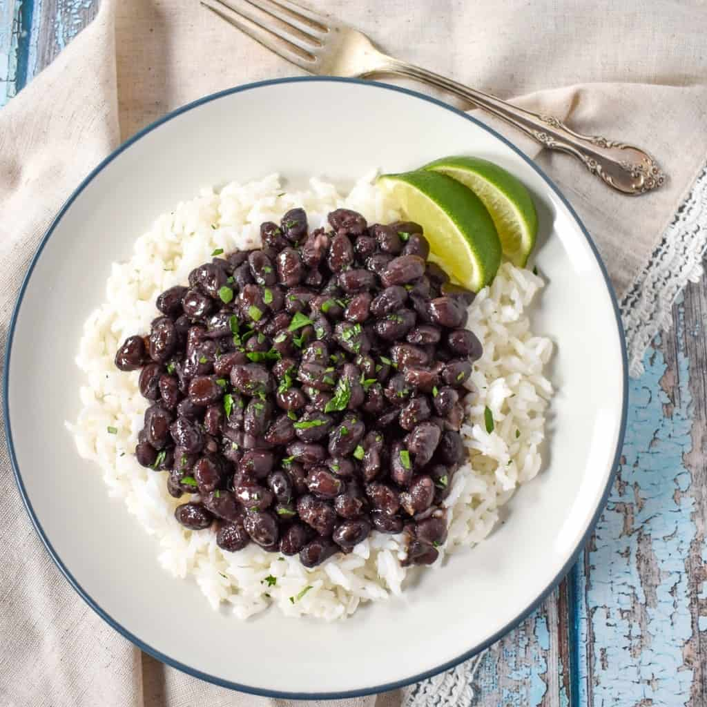An image of black beans over white rice with two lime wedges, served on a white plate with a blue rim. The plate is set on a blue wood table with a beige linen and a fork to the top right.