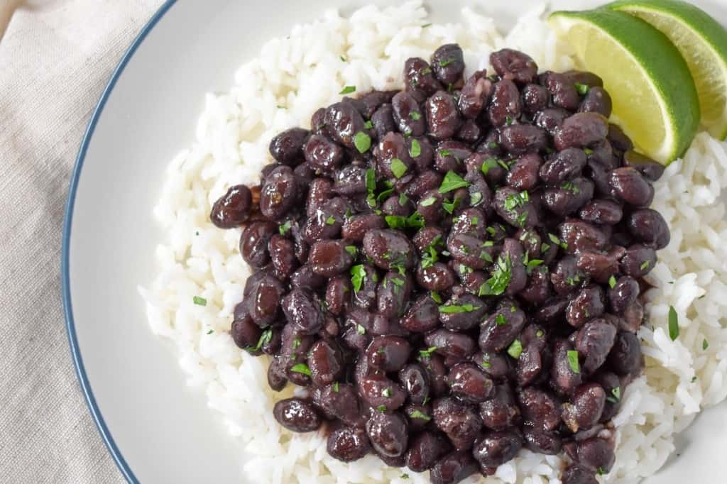 A close-up image of the black beans served over white rice, garnished with chopped parsley with two lime wedges on the side. The food is served on a white plate with a light blue rim.