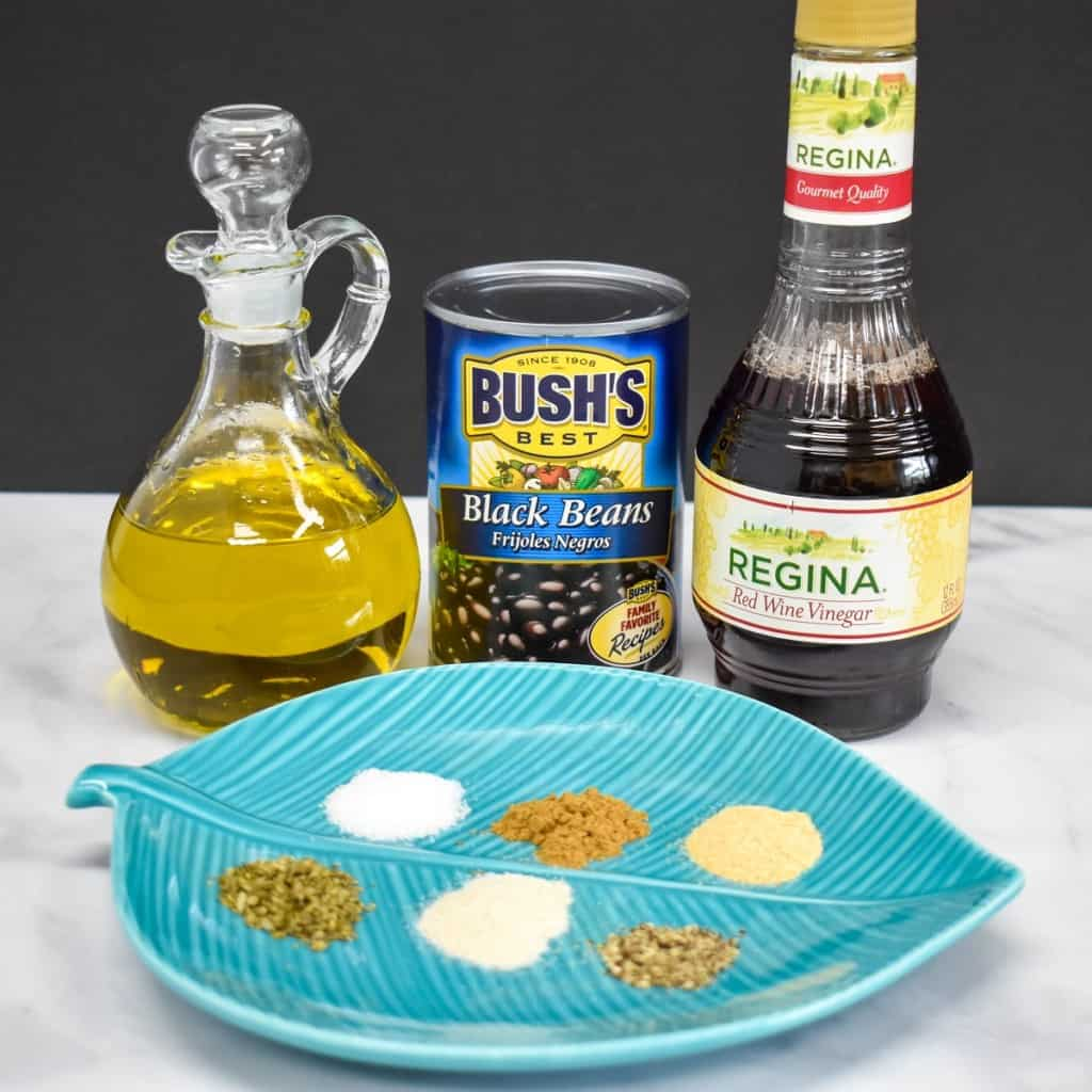 The ingredients for the quick Cuban style black beans on a white table with a black background. The spices are arranged in small piles on an aqua, leaf shaped plate.