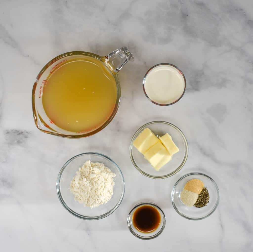 The ingredients for the gravy, prepped and arranged in glass bowls on a white table.