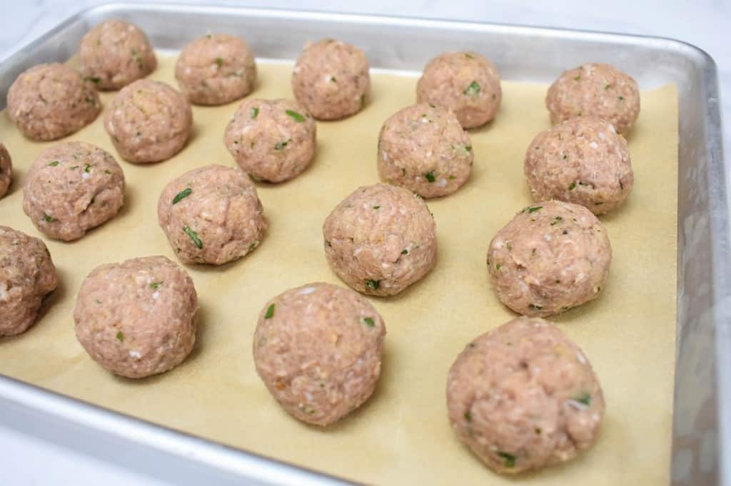 The formed turkey meatballs neatly arranged on a baking sheet that is lined with parchment paper.