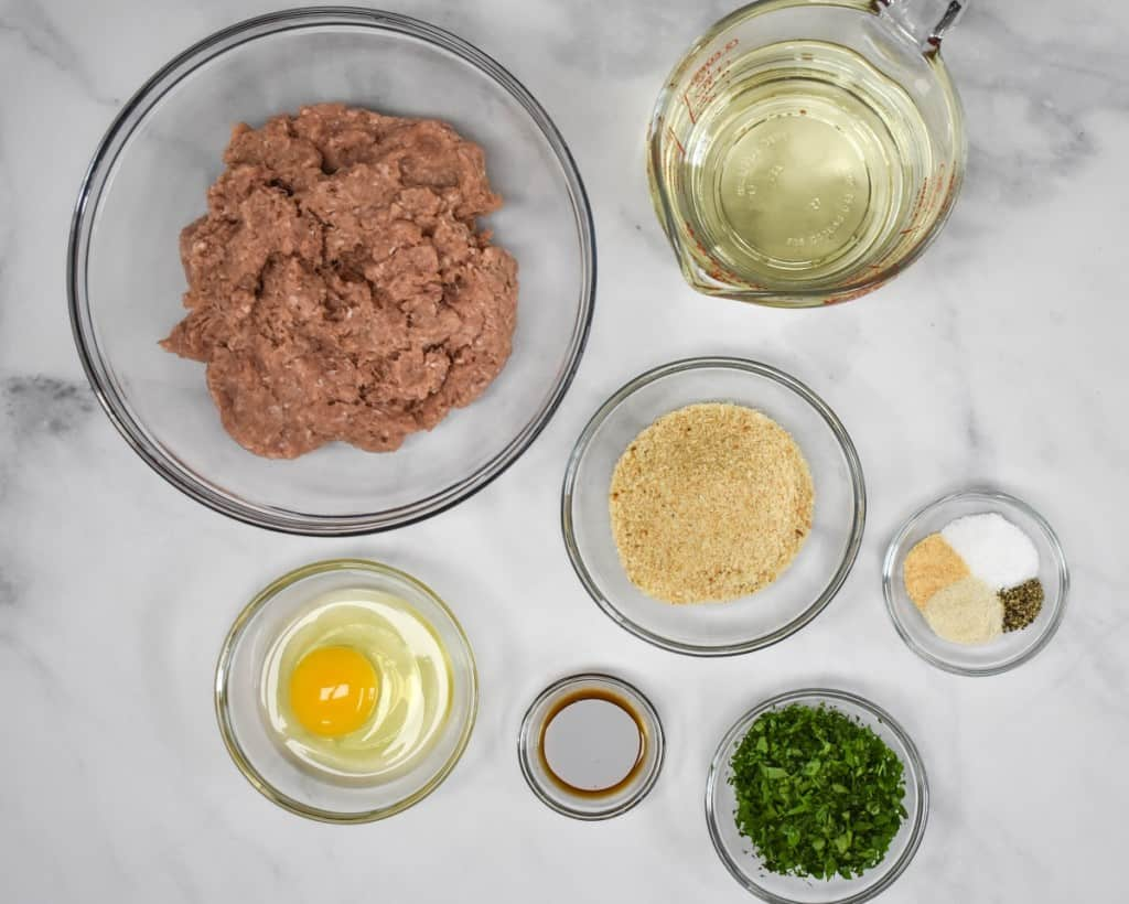 The ingredients for the meatballs, prepped and arranged in glass bowls on a white table.