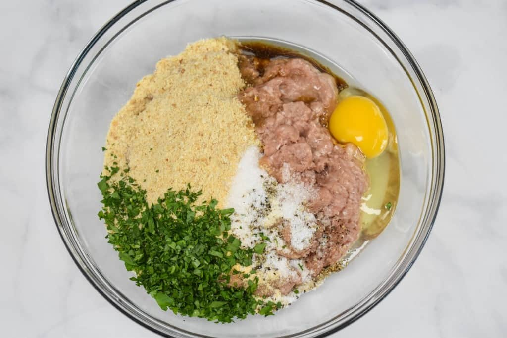 The ingredients for the meatballs added to a large, glass bowl but not yet combined.