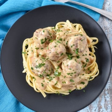 The turkey meatballs with gravy garnished with chopped parsley and served on a black plate and set on an aqua linen.