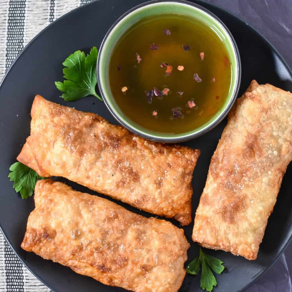 Three egg rolls set on a black plate with a small green bowl with sauce in it.