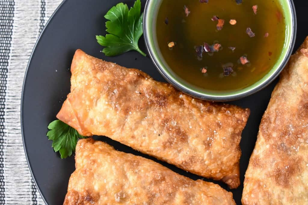 A close up image of the egg rolls set on a black plate with a small green bowl with sauce.