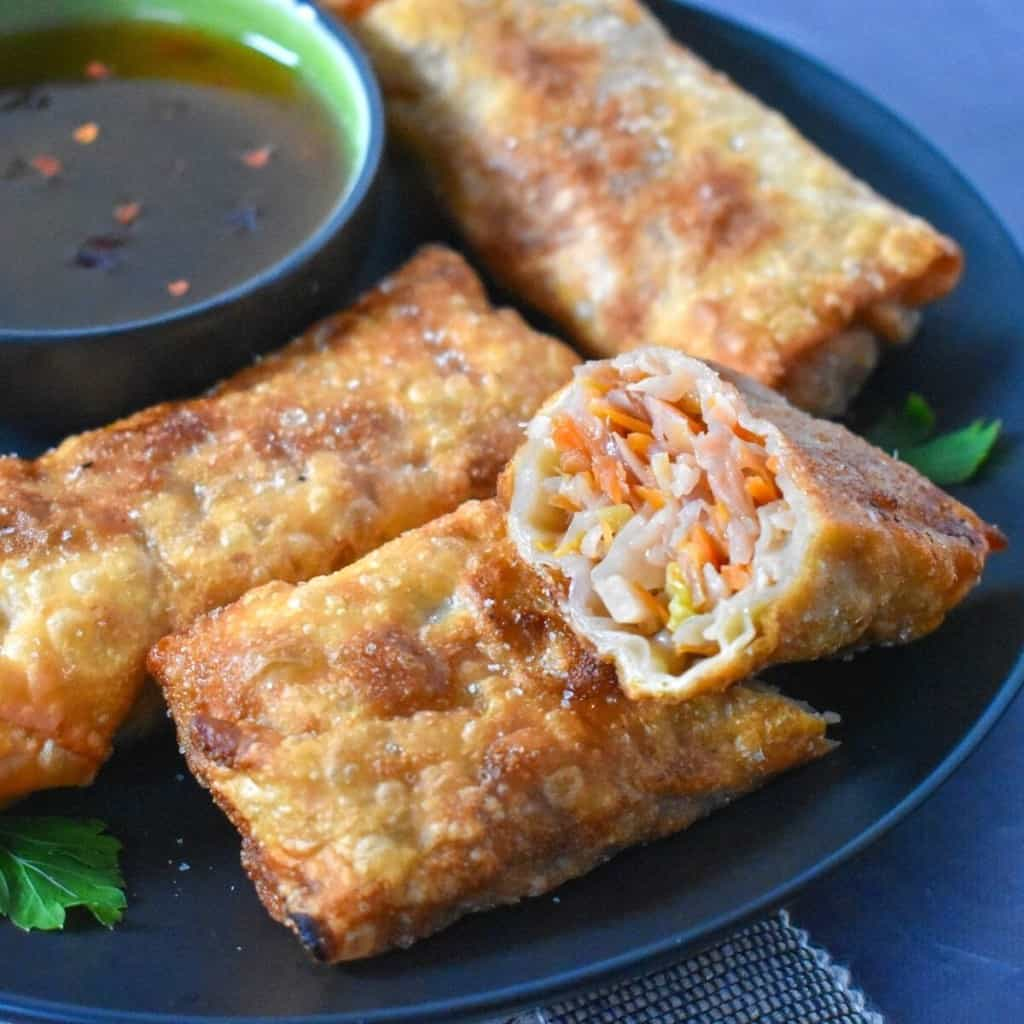 An image of the egg rolls set on a black plate with a green bowl with sauce. One of the egg rolls is cut in half showing the vegetable filling.
