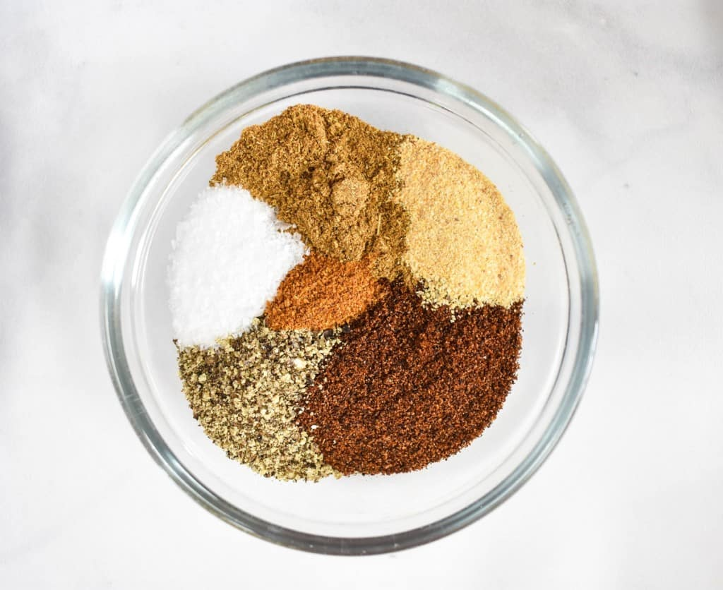 A close up image of the seasoning used in the recipe in a small glass bowl set on a white table.
