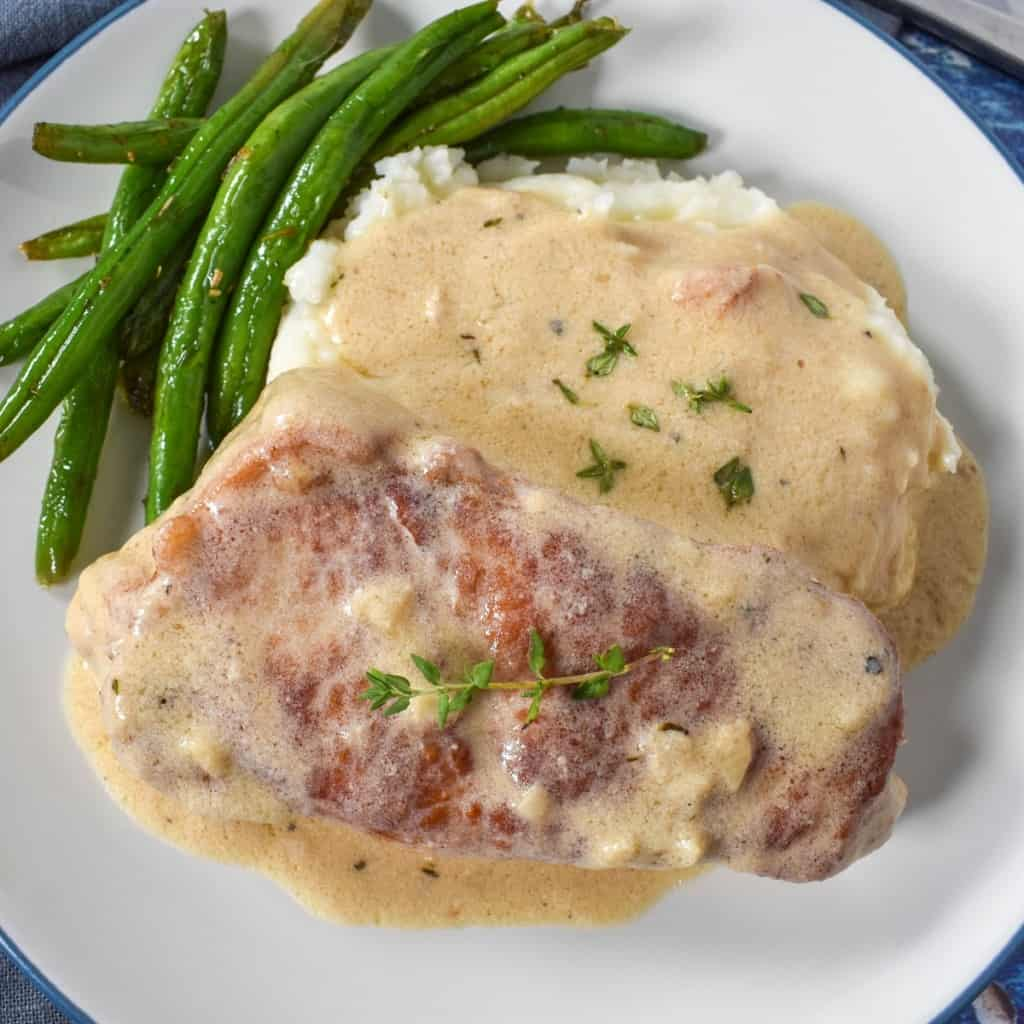 A close up image of the creamy pork chop served on a bed of mashed potatoes with a side of green beans on a white plate.