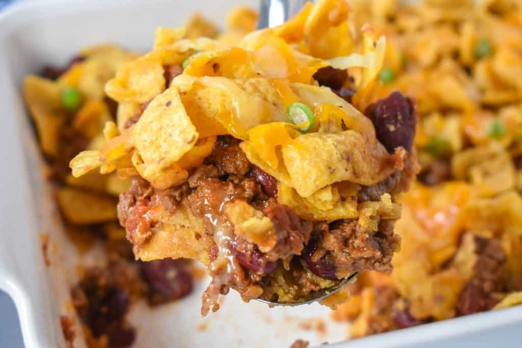 A scoop full of the frito pie held up with a serving spoon with the rest of it still in a white casserole dish.